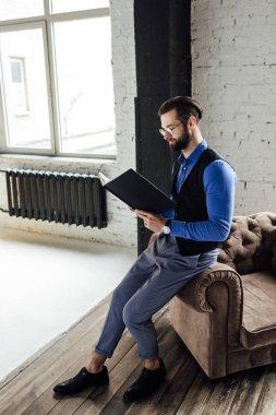 fashionable elegant businessman reading notebook in loft interior