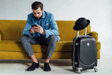 handsome stylish businessman using smartphone and sitting on sofa with luggage