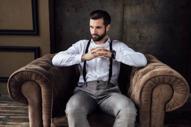 handsome fashionable man thinking and sitting in armchair