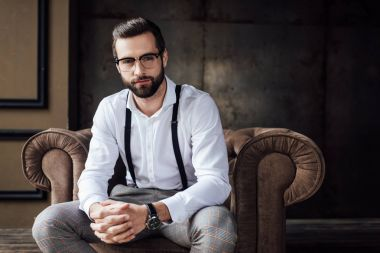handsome stylish man in glasses and suspenders sitting in armchair