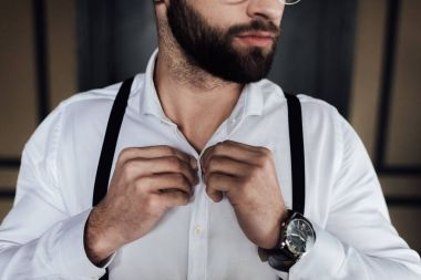 cropped view of bearded man in white shirt and suspenders