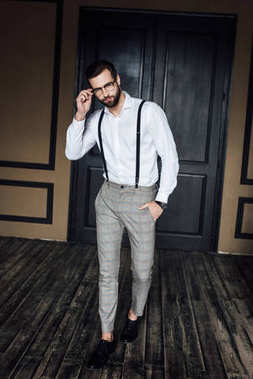 fashionable elegant man posing in white shirt and suspenders in loft interior