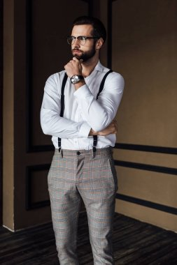 pensive fashionable man in trendy suspenders