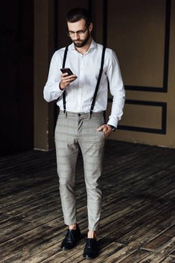 stylish bearded man in suspenders using smartphone in loft interior