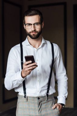 handsome bearded man in suspenders using smartphone and looking at camera