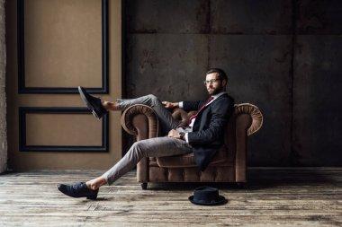 handsome elegant businessman posing in armchair, hat lying on floor near, loft interior