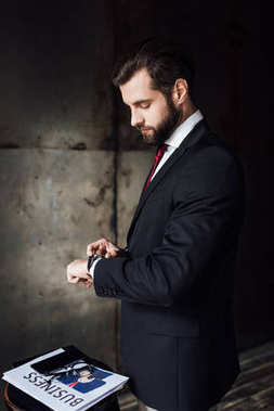 bearded businessman looking at wristwatch while standing at stool with business newspaper and smartphone