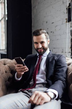 handsome smiling businessman using smartphone and sitting in armchair