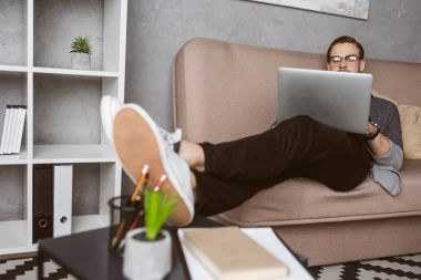 stylish young freelancer working with laptop on couch