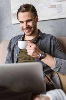 happy man working with laptop and drinking coffee on couch