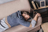 Fotografie young overworked businessman sleeping on couch with head lying on laptop
