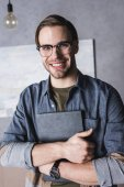 Fotografie smiling young man in eyeglasses holding book