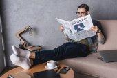 Fotografie mladý podnikatel naboso čtenářský deník na gauči