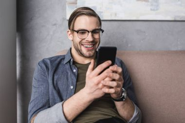 happy young man using smartphone while sitting on couch