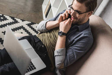 high angle view of handsome man working with laptop and talking by phone on couch