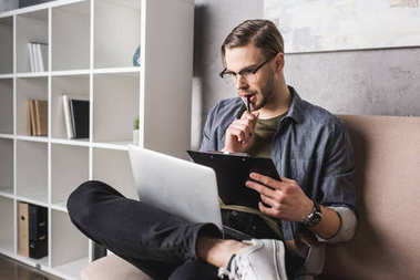 young thoughtful man working with laptop on couch and making notes on clipboard