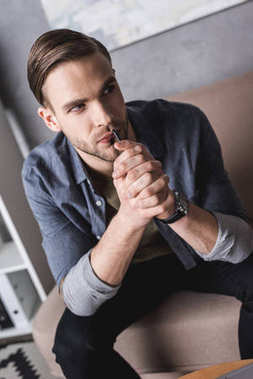 thoughtful young man with smartphone in hands waiting for call