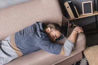 young overworked businessman sleeping on couch with head lying on laptop
