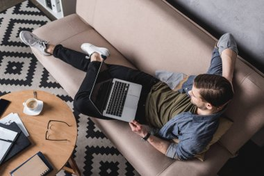 high angle view of young man working with laptop on couch