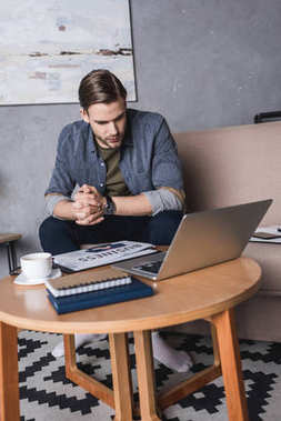 young businessman looking at laptop while sitting on couch