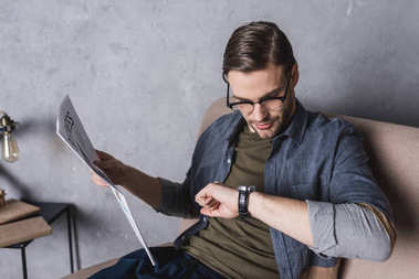 young businessman with newspaper checking time on his watch