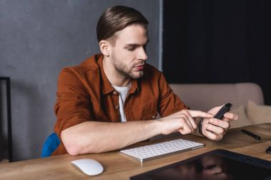 young handsome designer using calculator at workplace
