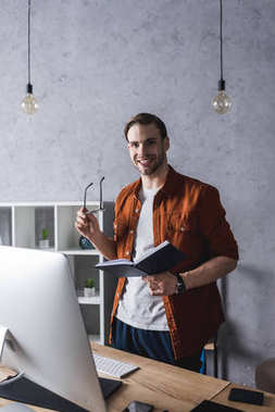 handsome young businessman with book at modern office