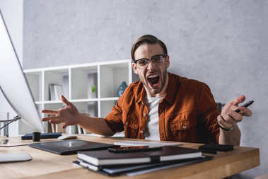 angry designer sitting at workplace and screaming at camera
