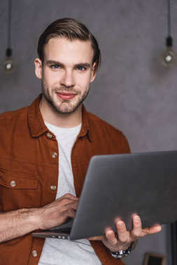 close-up portrait of handsome man with laptop looking at camera