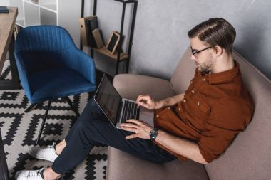 young handsome freelancer working with laptop on couch at home office