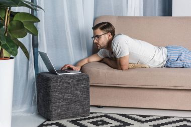 young attractive freelancer in pajamas working with laptop on couch