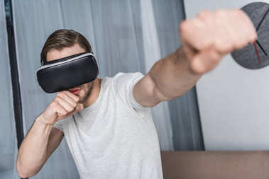 handsome young man in virtual reality headset playing fighting game