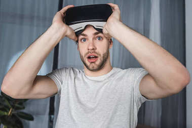 shocked young man in virtual reality headset
