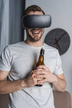 young happy man with bottle of beer in virtual reality headset