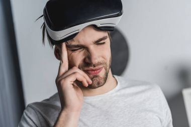 young man in virtual reality headset having headache