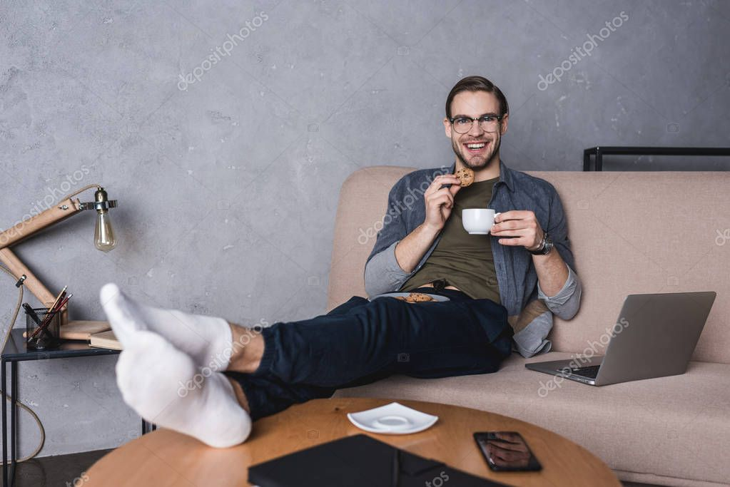 young handsome man with laptop  drinking coffee with cookies on couch