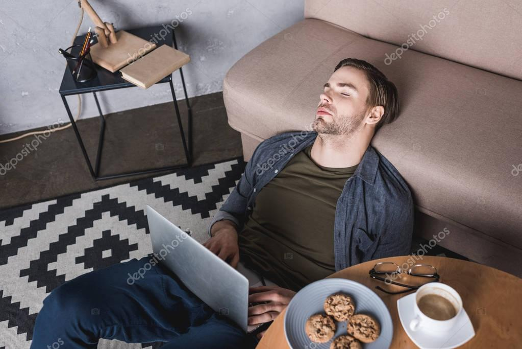 young overworked man sleeping on floor with laptop