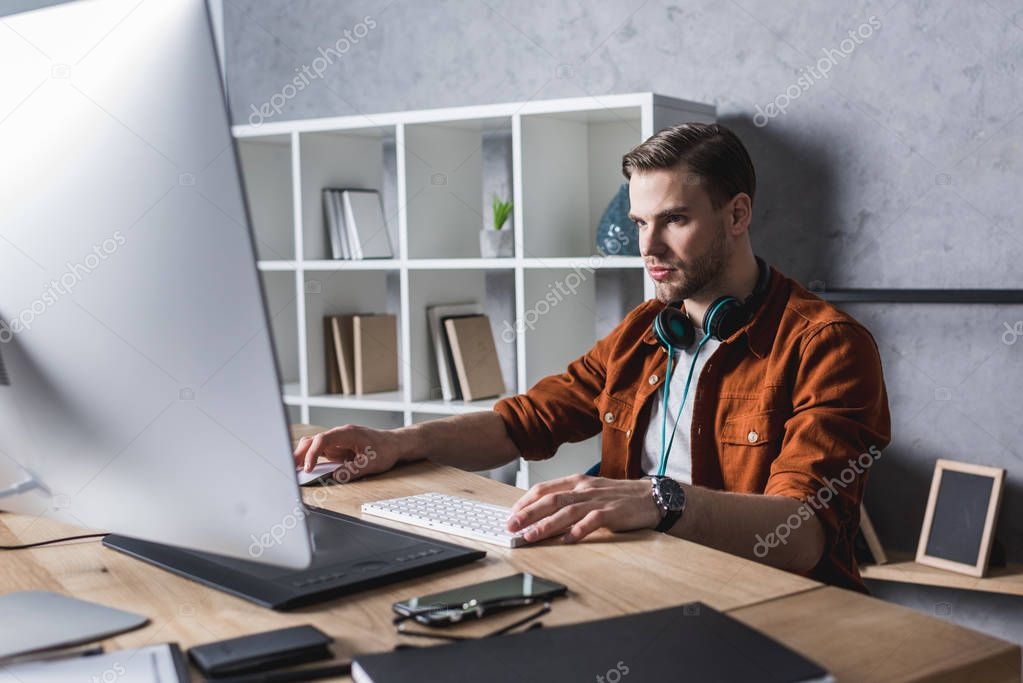handsome young designer wrking wit computer at modern office