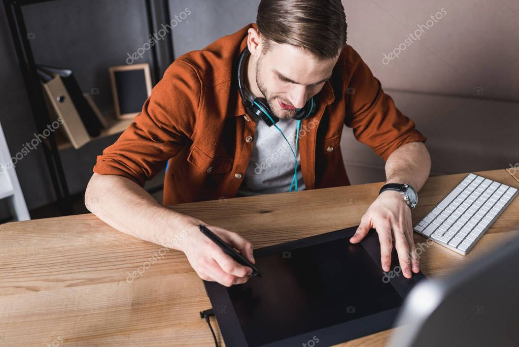 high angle view of young designer working with computer and drawing tablet