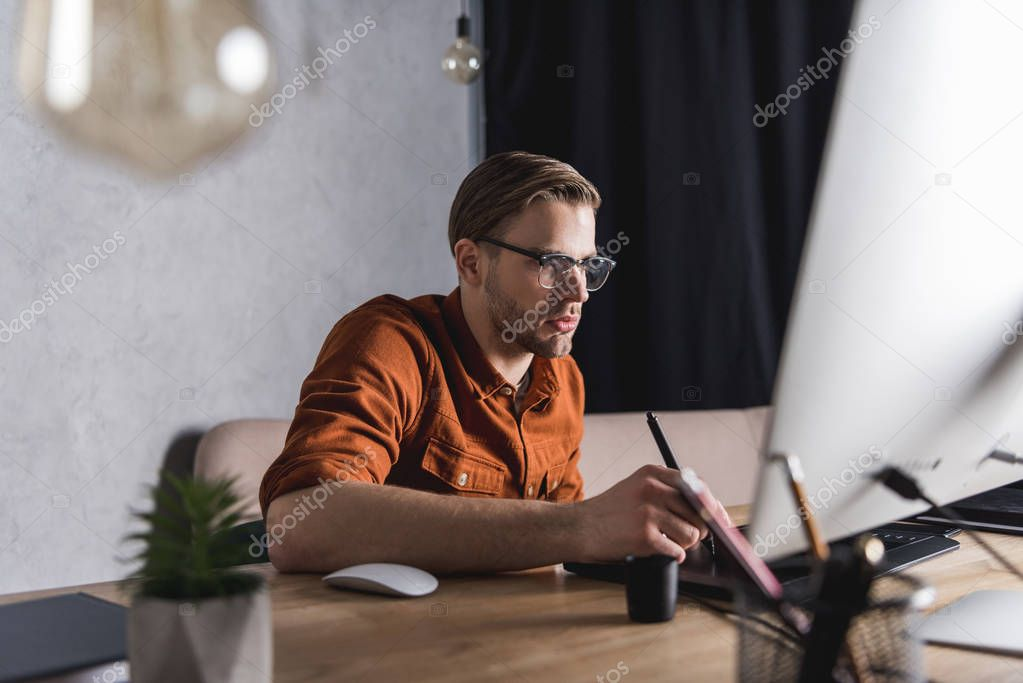 stylish young designer working with drawing tablet at workplace