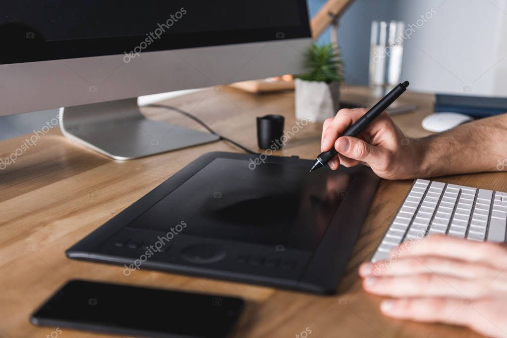 cropped shot of designer working with drawing tablet at workplace