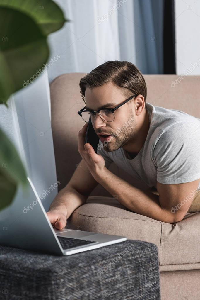 young freelancer working with laptop and talking by phone on couch