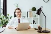 Fotografie usmíval se podnikatel pracovat s notebookem na pracovišti v moderní kanceláři