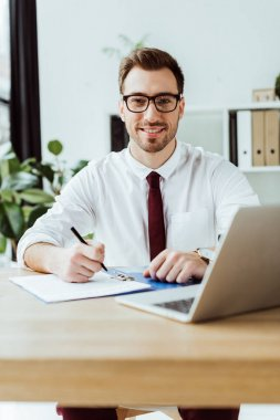 handsome smiling businessman writing in documents at workspace with laptop