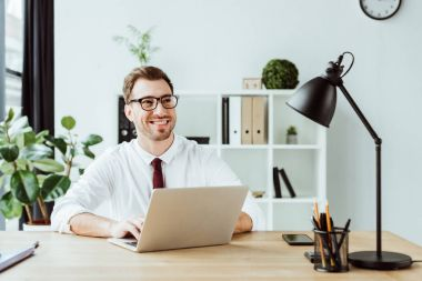 smiling businessman working with laptop at workplace in modern office