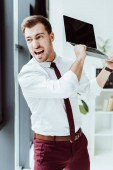 aggressive businessman yelling and throwing laptop in office