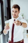 Photo smiling businessman with disposable cup of coffee pointing at you