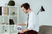 pohledný podnikatel poslech hudby ve sluchátkách a čtenářský deník