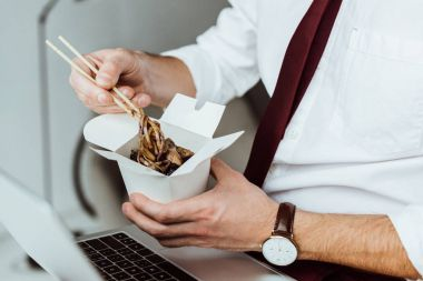 cropped view of businessman with laptop eating noodles in office