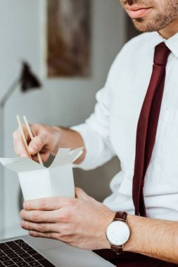 cropped view of businessman holding box with noodles for lunch